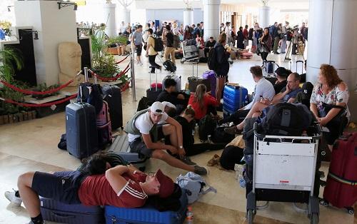Du khách nằm, ngồi la liệt trên sàn nhà trong lúc chờ đợi chuyến bay ở sân bay quốc tế Lombok sáng nay. Ảnh: Reuters.