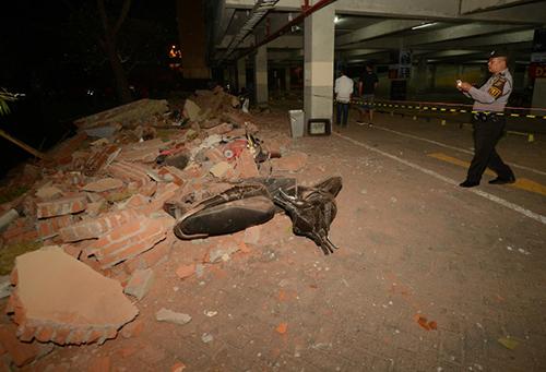 Cảnh sát kiểm tra thiệt hại tại một trung tâm thương mại ở thủ phủDenpasar, đảo Bali, tối qua sau động đất. Ảnh: AFP