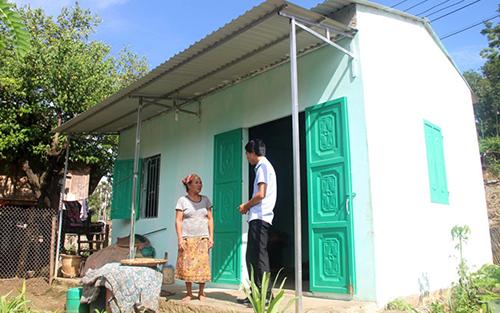 Bà Hà Thị Phai bên căn nhà mới được Thủ tướng tặng kinh phí xây dựng. Ảnh: Lam Sơn.
