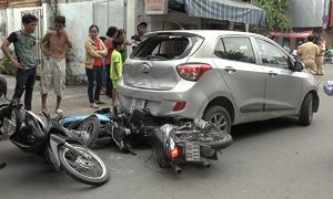 Ôtô lùi cuốn ba xe máy trên đường Sài Gòn