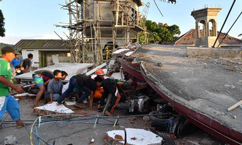 Lực lượng cứu hộ và người dân tìm cách tiếp cận người còn sống và các thi thể dưới đống đổ nát trên đảo Lom bok hôm 5/8. Ảnh: PressTV.