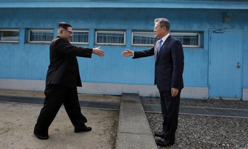 Lãnh đạo Triều Tiên Kim Jong-un (trái) chuẩn bị bắt tay Tổng thống Hàn Quốc Moon Jae-in hôm 27/4tạiPanmunjom. Ảnh:AFP.