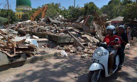 Người dân đảo Lombok, Indonesia, đi qua những tòa nhà đổ nát sau cơn dư chấn mạnh 5,9 độ hôm nay. Ảnh: AFP.
