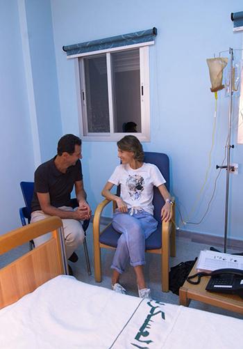 Bà Asma ngồi cạnh ông Assad khi đang truyền tĩnh mạch