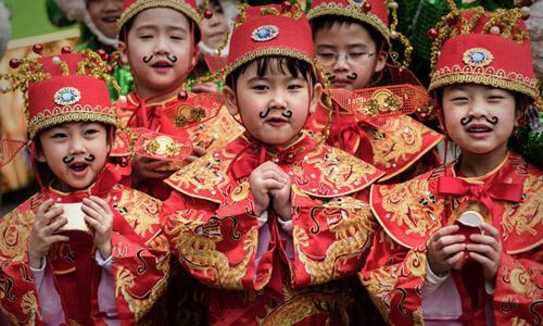 Trẻ em Trung Quốc mặc trang phụchóa trang truyền thống đón năm mới 2017. Ảnh: AFP.