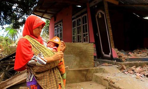 Người phụ nữ bế đứa con sơ sinh bên ngôi nhà đổ nát do động đất ở đảo Lombok, Indonesia tối 5/8. Ảnh: CNN.