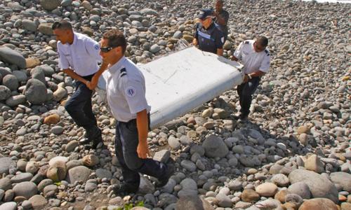 Các sĩ quan Pháp khiêng một mảnh vỡ của máy bay MH370 trên đảo Reunion ở Ấn Độ Dương hồi tháng 7/2015. Ảnh: AP.