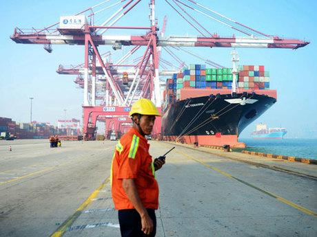 Công nhân Trung Quốc đứng cạnh tàu hàng ở cảng Thanh Đảo tháng 7/2017. Ảnh: AFP.