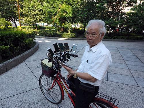 Ông Chen và chiếc xe đạpgắn 11 chiếc điện thoại để đi bắt Pokemon. Ảnh: EPA