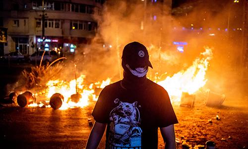 Một người đàn ông đứng trước một đám cháy trong vụ đụng độ giữa đám đông biểu tình và cảnh sát tại thủ đô Bucharest, Romania ngày 10/8. Ảnh: AFP.