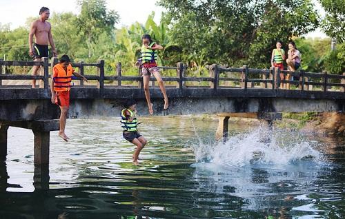 Trẻ Quảng Nam tắm ở kênh trong mùa nóng với sự giám sát của bố mẹ. Ảnh: Đắc Thành