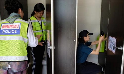Cảnh sát và tình nguyện viên rà soát các camera quay lén tại một nhà vệ sinh ở bể bơi công cộng thành phố Changwon hôm 23/7. Ảnh: Washington Post