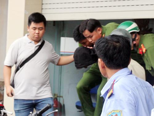 Cảnh sát đưa thanh niên trùm mũ đen về trụ sở. Ảnh: Duy Trần