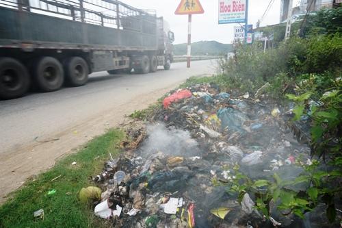 Một đống rác đang cháy ngún bên quốc lộ 1 qua huyện Đức Phổ. Ảnh: Phạm Linh.
