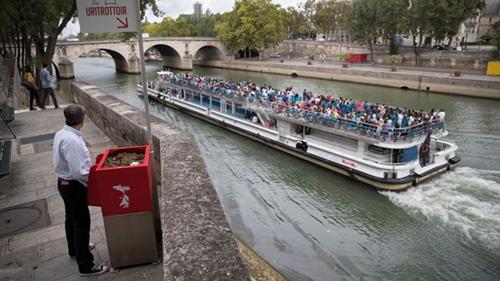 Một người đàn ông sử dụng bốt tiểu tiện mới được lắp đặt bên sông Seine ở Paris. Ảnh: AFP