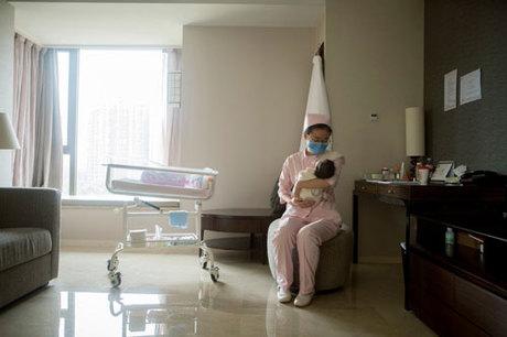 Nữ hộ lý chăm sóc trẻ sơ sinh tại một bệnh viện phụ sản ở Bắc Kinh. Ảnh: NYTimes.