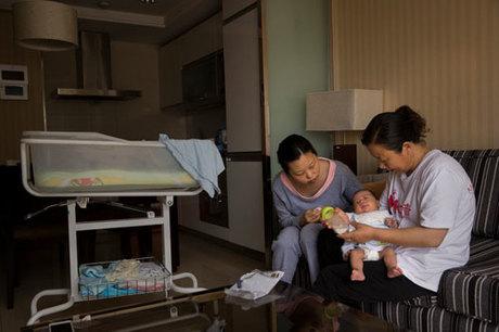 Bảo mẫu (phải) hướng dẫn bà mẹ trẻ cách chăm sóc trẻ sơ sinh ở Bắc Kinh năm 2015. Ảnh: NYTimes.
