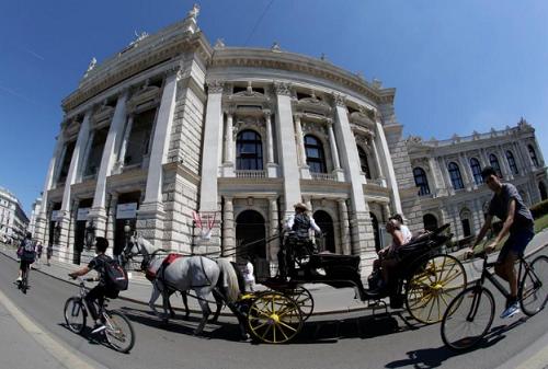 Xe ngựa Fiaker truyền thống đi qua nhà hát Burgtheater ở Vienna hôm 13/8. Ảnh: Reuters.