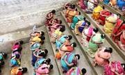 Hàng trăm phụ nữ Ấn Độ quỳ gối, ăn cơm trộn cát cầu thần ban con