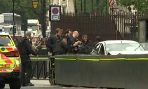 Cảnh sát vũ trang bao vây chiếc xe đâm vào rào chắn bên ngoài tòa nhà quốc hội Anh sáng nay. Ảnh: ITV.