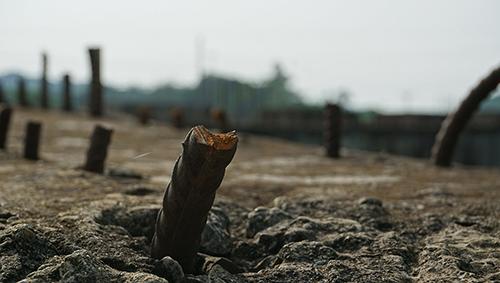 Nhiều vị trí ở mố cầu đã xuống cấp. Các cây thép chờ ở mố chân cầu phía Tây bị kẻ gian cắt cụt. Ảnh: Lê Hoàng.
