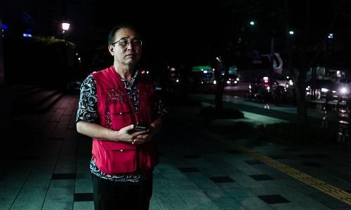 Kim Jeong-cheol đợi khách gọi lái xe thuê buổi đêm ở Seoul. Ảnh: Guardian.