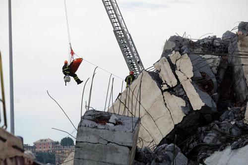 Nhân viên cứu hộ đưa nạn nhânra khỏi đống đổ nát sau vụ sập cầu Morandi hôm 14/8. Ảnh: AFP.