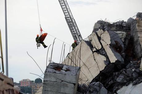 Nhân viên cứu hộ đưa nạn nhân ra khỏi đống đổ nát sau vụ sập cầu Morandi hôm 14/8. Ảnh: AFP.