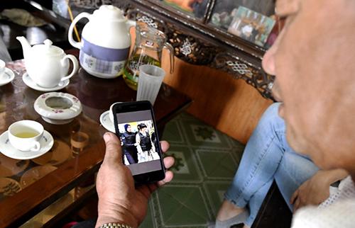 Ông Thạnh xem một bức ảnh chụp con gái khi theo dõi tin tức về phiên tòa hôm nay ở Malaysia. Ảnh: AFP
