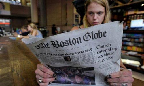Một độc giả đọc số báo ngày 15/8 của tờ Boston Globe. Ảnh: AFP.