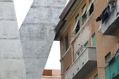 Một trụ cầu Morandi tựa vào tòa chung cư cũ dưới chân cầu. Ảnh: Mirror