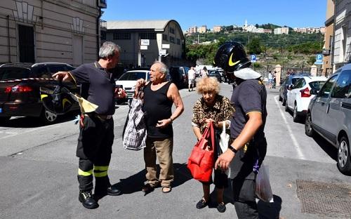 Một đôi vợ chồng lớn tuổi trò chuyện với lực lượng cứu hộ tại Genoa hôm 15/8, khi đang đợi vào nhà để lấy đồ. Ảnh: AFP.