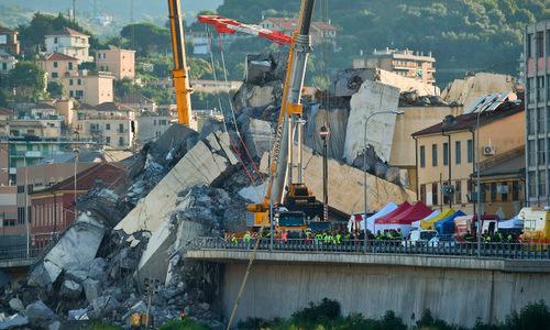 Cần cẩu di chuyển các khối bê tông tại hiện trường sập cầu hôm 16/8. Ảnh: Reuters.
