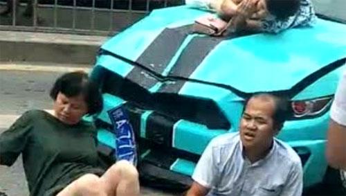 Đầu xe thể thao móp nặng, trong khi các nạn nhân nằm hoặc ngồi la liệt trên đường, một phụ nữ vẫn nằm trên nắp ca-pô. Ảnh: QQ.