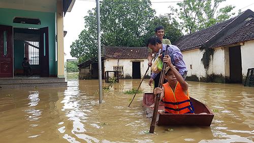 Người dân dùng thuyền thúng di chuyển trong nước lũ ở Thiệu Dương. Ảnh: Lê Hoàng.
