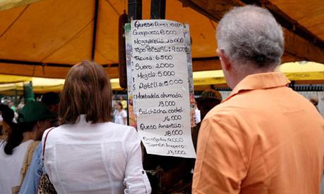 Người dân xem bảng giá tại một khu chợ ở thủ đô Caracas, Venezuela hôm 18/8. Ảnh: Reuters.