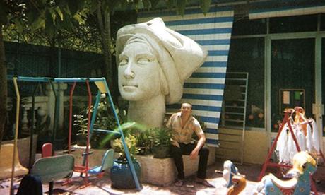 Hưng Lê chụp cùng bức tượng Cô gái Việt Nam đặt trong khuôn viên một trường tiểu học đầu những năm 1990. Ảnh: NVCC.