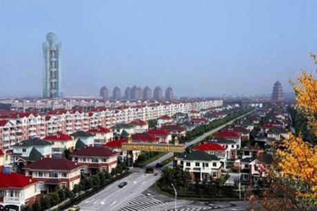 Từng dãy biệt thự và chung cư xếp thẳng tắp trong thôn Hoa Tây, phía xa là khách sạn chọc trời cao hơn 300 mét. Ảnh: Sina.