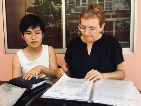 Bà Agnès Munier-Michel (phải) ngồi tại ban công khách sạn ở quận Tân Bình hôm 2/8 lật giở tập hồ sơ điều trị bệnh não úng thủy của con gái Tường Vy Munier-Michel. Ảnh: Hạnh Phạm.