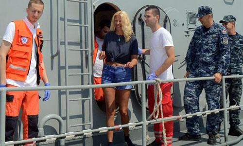 Nữ du khách Kay Longstaff cùng các nhân viên cứu hộ và cảnh sát biển Croatia trên tàu cứu hộ sau khi được giải cứu sáng 19/8. Ảnh: AFP.