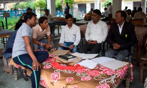 Các nhân viên của Jan Sahas ngồi bên ngoài một tòa án địa phương ở Bharatpur phân tích hồ sơ vụ kiện với luật sư Pohiya. Ảnh: CNN.