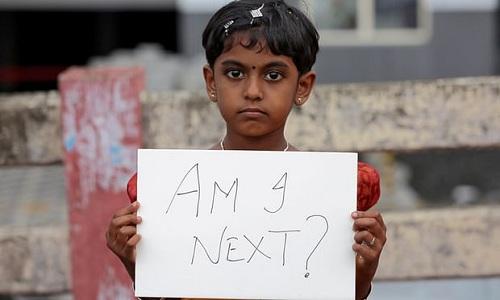 Một bé gái ở Kochi, bang tây nam Kerala cầm biểu ngữ Liệu em có phải nạn nhân tiếp theo phản đối tình trạng bạo lực tình dục phụ nữ và trẻ em, sau vụ 8 gã hiếp dâm tập thể một bé gái 8 tuổi người Hồi giáo ở bang Jammu - Kashmir hôm 16/8. Ảnh: Reuters.