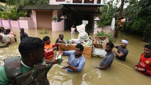 Người dân vùng ngập lũ ở Kerala nhận lương thực cứu trợ. Ảnh: AP.