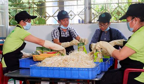 Anh Tiêu Thanh Vũ (thứ 2 từ trái sang) chính là cha đẻ của chiếc máy làm giá đỗ tự động. Ảnh: Bizmedia