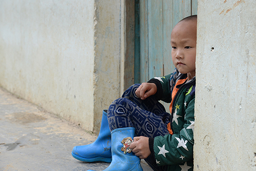 [Caption]A boy sits in front of a door in Hechi, Guangxi, on April 20. The boy is one of 200 students at Shang Zhen primary school, where most of the children have parents who have left for work in Chinas bigger cities. Photo: Visual China