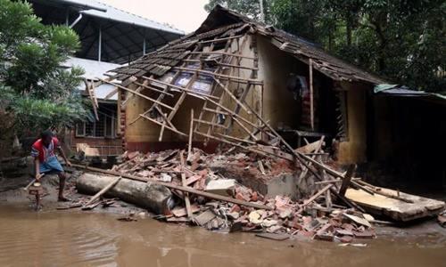 Người đàn ông dọn dẹp mảnh vỡ từ ngôi nhà bị sập do lũ ở Paravur, bang Kerala, Ấn Độ hôm 23/8. Ảnh: Reuters.