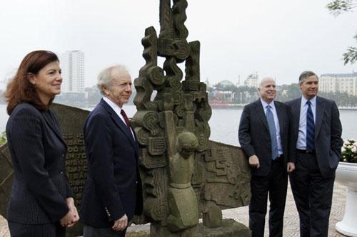 McCain (thứ hai từ phải sang) chụp ảnh tại tượng đài phi công Mỹ bị bắn rơi ở hồ Trúc Bạch vào năm 2012. Ảnh: Đại sứ quán Mỹ.