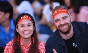 Khách Tây đeo băng rôn cổ vũ Olympic Việt Nam trên phố Nguyễn Huệ