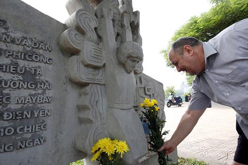 Robert Gibb đặt hoa tưởng niệm thượng nghị sĩ John McCain tại phù điêu bên hồ Trúc Bạch sáng 26/8. Ảnh: Reuters.