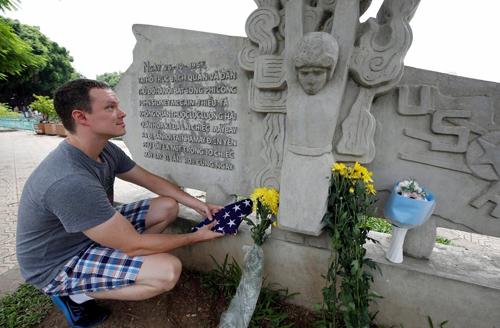 Giáo viên tiếng Anh Derek Davis đặt cờ và hoa tưởng nhớ ông McCain. Ảnh: Reuters.